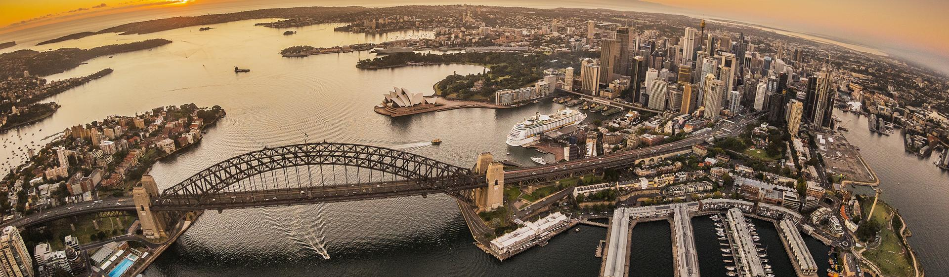 Aerial of the sun rising over Sydney Harbour with views of the Sydney Harbour Bridge, the CBD and Walsh Bay